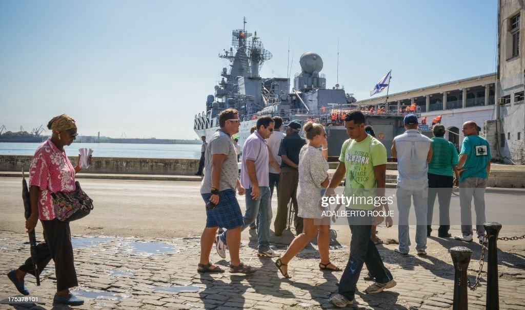 Cubans watch as the 'Moskva' Russian guide missile cruiser (R) moors at Havana's harbour, on August 3, 2013. The vessel is part of a three-ship group in official visit to Cuba. AFP PHOTO/Adalberto ROQUE