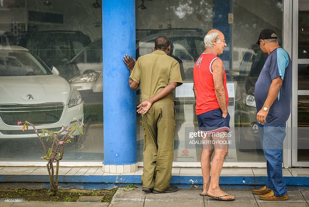 Cubans watch new and used cars for sale at a car dealer in Havana on January 3, 2014. The free sale of cars in Cuba has been officially authorized Friday, but at astronomical prices.