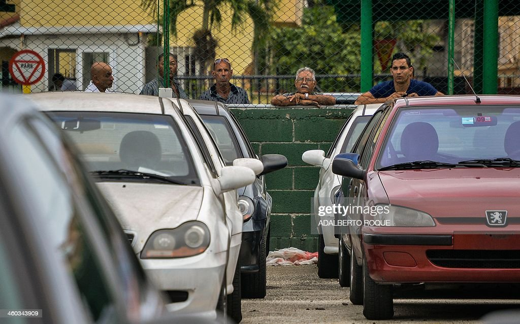 Cubans watch new and used foreign-made cars for sale at a car dealer in Havana on January 3, 2014. The free sale of cars in Cuba has been officially authorized Friday, but at astronomical prices.