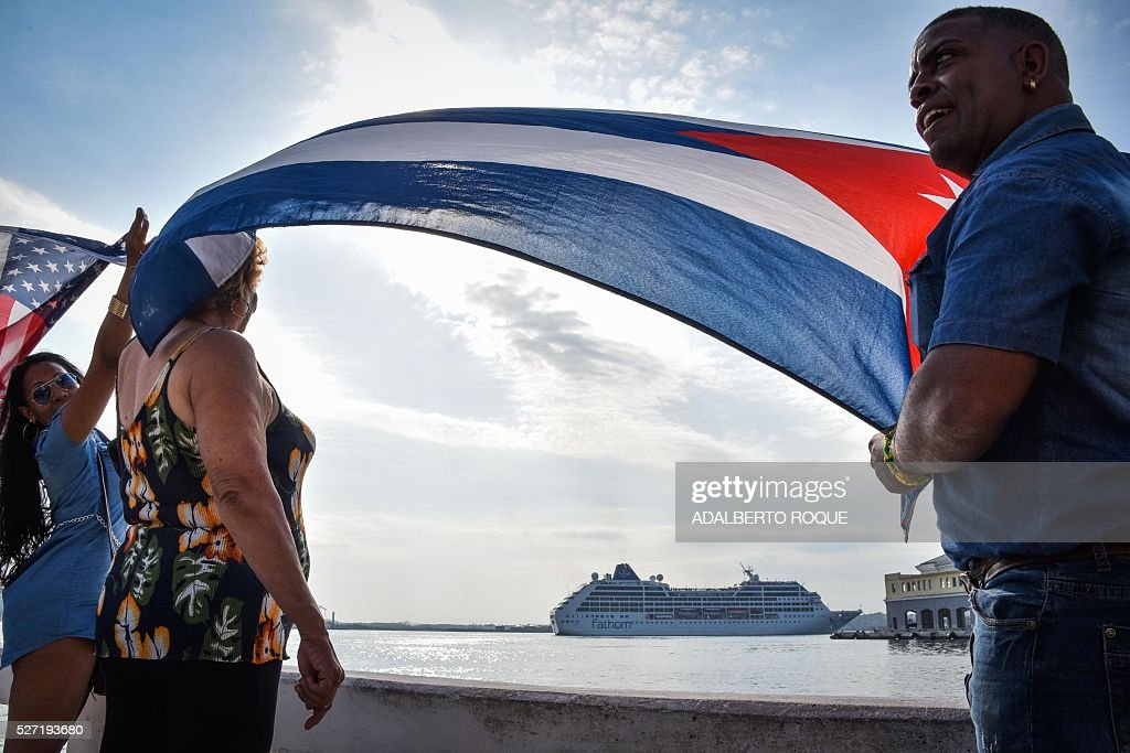 Cubans wave a US and a Cuban flag at the Malecon waterfront as the first US-to-Cuba cruise ship to arrive in the island nation in decades glides into the port of Havana, on May 2, 2016. The first US cruise ship bound for Cuba in half a century, the Adonia -- a vessel from the Carnival cruise's Fathom line -- set sail from Florida on Sunday, marking a new milestone in the rapprochement between Washington and Havana. The ship -- with 700 passengers aboard -- departed from Miami, the heart of the Cuban diaspora in the United States. / AFP / ADALBERTO