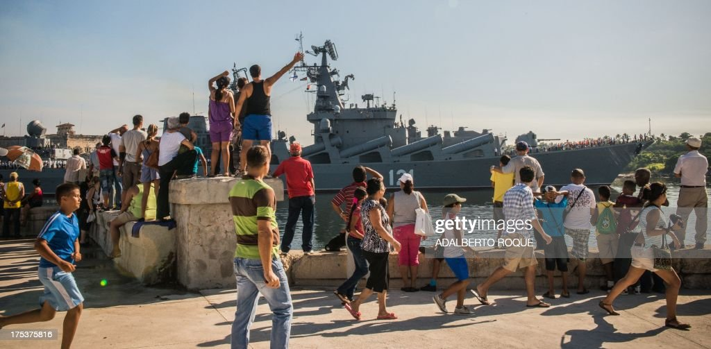 Cubans wave as the 'Moskva' Russian guide missile cruiser arrives at Havana's harbour, on August 3, 2013. The vessel is part of a three-ship group in official visit to Cuba. AFP PHOTO/Adalberto ROQUE