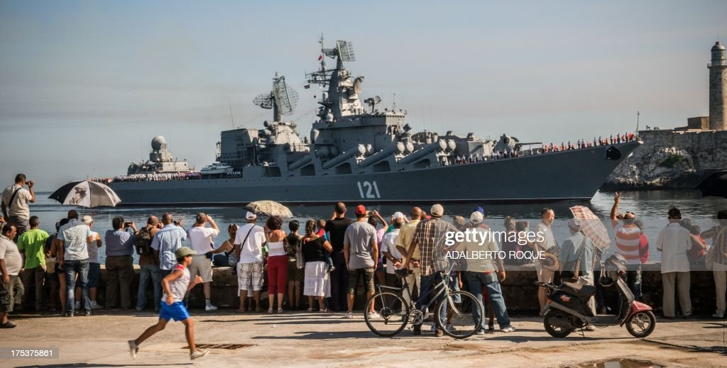 Cubans wave as the 'Moskva' Russian guided missile cruiser arrives at Havana's harbour, on August 3, 2013. The vessel is part of a three-ship group in official visit to Cuba. AFP PHOTO/Adalberto ROQUE