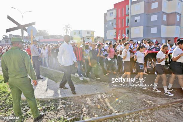 Cubans wave flags during a march in honor of late Cuban Revolution leader Fidel Castro as Cuba commemorates the first anniversary of Castros funeral...
