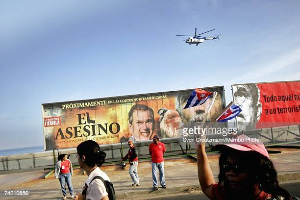 Cubans wave flags during an AntiTerrorism march on January 24 2006 past a political poster designed to look like a movie poster which 'announces' the...