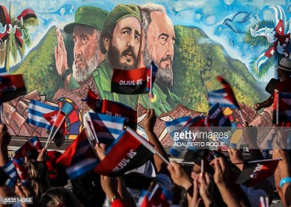 Cubans wave flags in front of a poster with images of former president Fidel Castro during the celebration of the 63rd anniversary of the guerrilla...