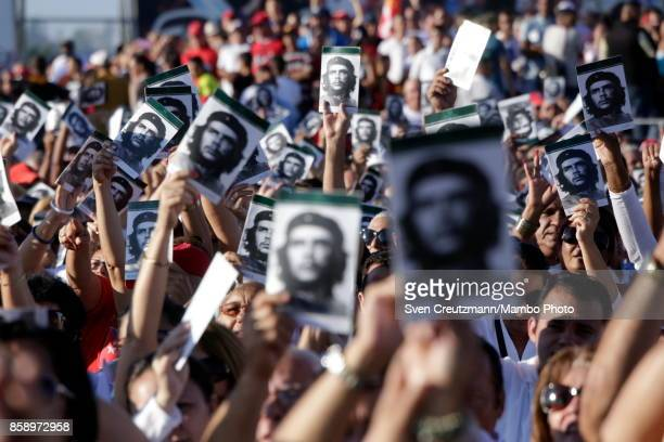 Cubans wave holding photos of Che Guevara during a political act at the Plaza de la Revolucion to celebrate the 50th anniversary of the death of...
