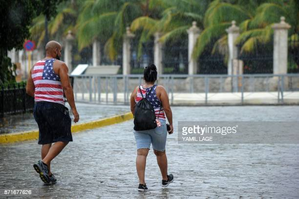 Cubans wearing sleeveless sweaters with the US flag design walk under the rain in Havana on November 8 2017 Tighter restrictions on US travellers to...