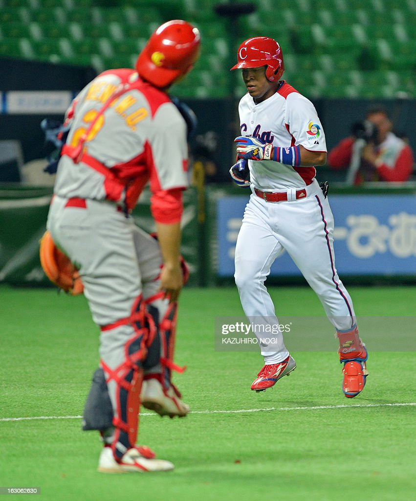 Cuba's Alexei Bell (R) comes into home after hitting a two-run home run as China's catcher Meng Weiqiang (L) looks on during the fourth inning of their first-round Pool A game in the World Baseball Classic tournament in Fukuoka on March 4, 2013.