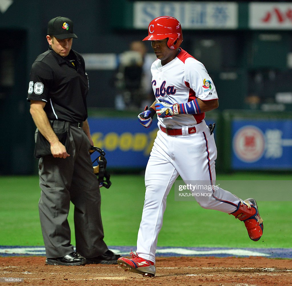 Cuba's Alexei Bell (R) crosses home plate to score after hitting a two-run home run during the fourth inning of their first-round Pool A game in the World Baseball Classic tournament in Fukuoka on March 4, 2013. AFP PHOTO / KAZUHIRO NOGI