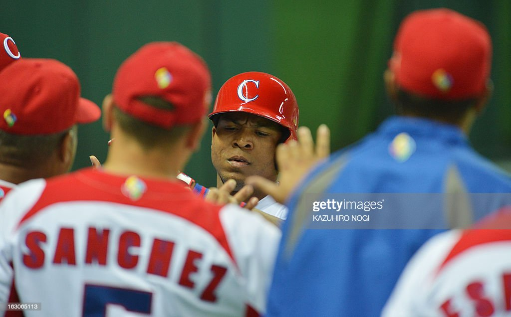Cuba's Alexei Bell (C) is congratulated by his teammates after his two-run home run against China during the fourth inning of their first-round Pool A game in the World Baseball Classic tournament in Fukuoka on March 4, 2013.