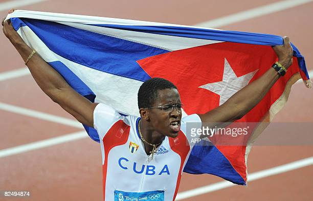 Cuba's Dayron Robles waves his national flag as he celebrates winning the men's 110m Hurdles final at the National stadium as part of the 2008...