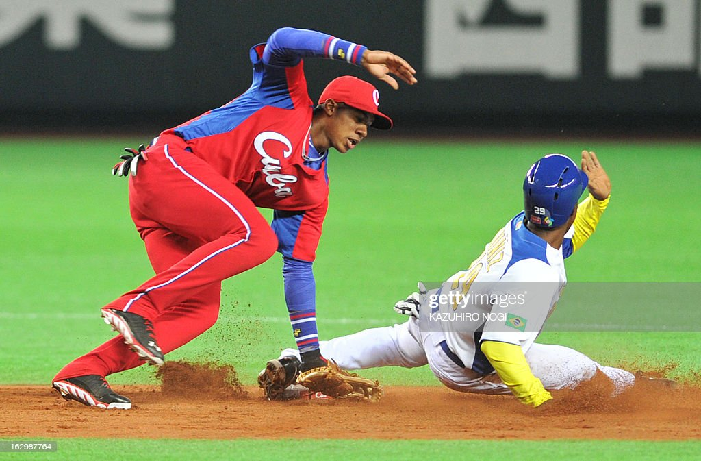Cuba's Erisbel Arruebarruena (L) tags out Brazil's JC Muniz (R) during the second inning of their first-round Pool A game in the World Baseball Classic tournament in Fukuoka on March 3, 2013. AFP PHOTO / KAZUHIRO NOGI