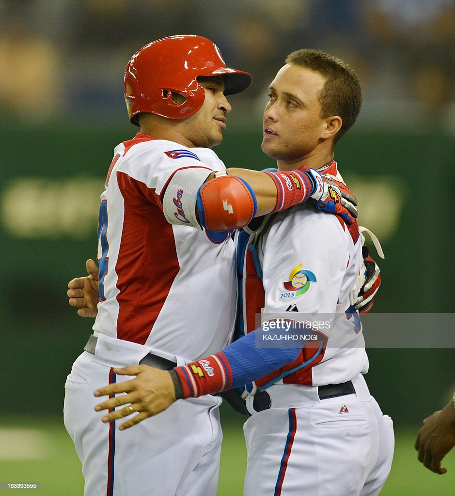 Cuba's Frederich Cepeda (L) celebrates his two-run homer with catcher Frank Morejon during the first inning of their second-round Pool 1 game against Taiwan in the World Baseball Classic tournament at the Tokyo Dome on March 9, 2013. AFP PHOTO / KAZUHIRO NOGI