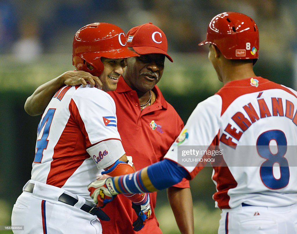 Cuba's Frederich Cepeda (L) celebrates his two-run homer with Jose Fernandez (R) and a coach during the first inning of their second-round Pool 1 game against Taiwan in the World Baseball Classic tournament at the Tokyo Dome on March 9, 2013. AFP PHOTO / KAZUHIRO NOGI