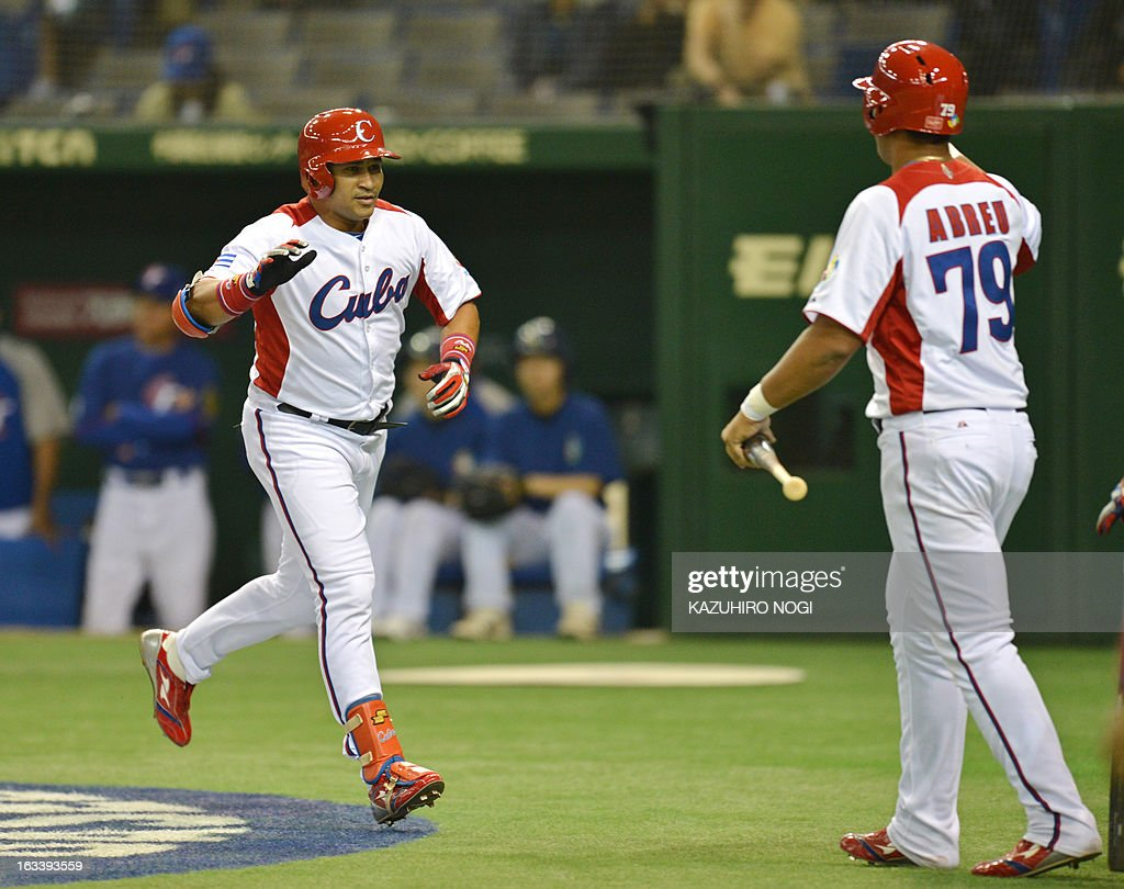 Cuba's Frederich Cepeda (L) scores as he is congratulated by teammate Jose Abreu (R) after his two-run homer against Taiwan during the first inning of their second-round Pool 1 game in the World Baseball Classic tournament at the Tokyo Dome on March 9, 2013. AFP PHOTO / KAZUHIRO NOGI