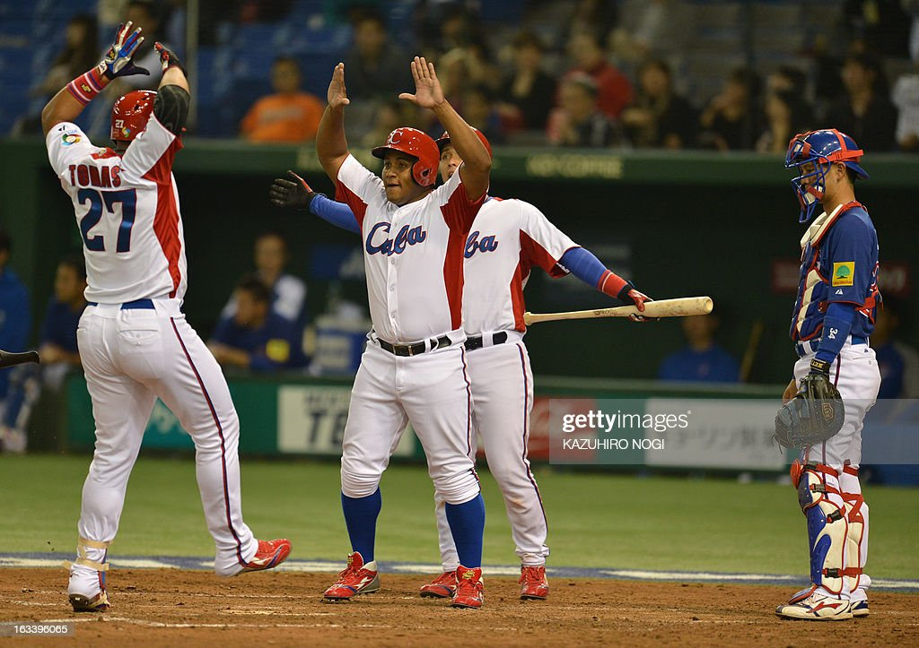 Cuba's outfielder Yasmany Tomas (L) arrives at home-plater after his three-run homer against Taiwan as he is welcomed by teammate Frederich Cepeda (C) during the fourth inning of their second-round Pool 1 game in the World Baseball Classic tournament at the Tokyo Dome on March 9, 2013. AFP PHOTO / KAZUHIRO NOGI