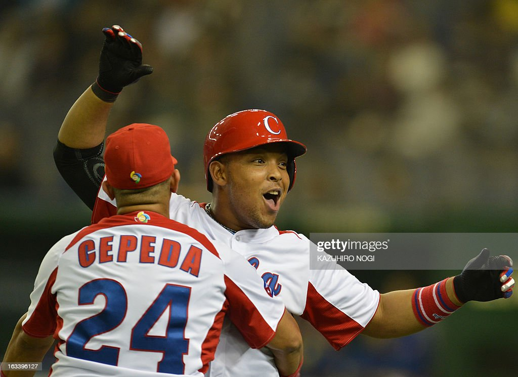 Cuba's outfielder Yasmany Tomas (C) is congratulated by teammate Frederich Cepeda (L) after his three-run homer against Taiwan during the fourth inning of their second-round Pool 1 game in the World Baseball Classic tournament at the Tokyo Dome on March 9, 2013. AFP PHOTO / KAZUHIRO NOGI