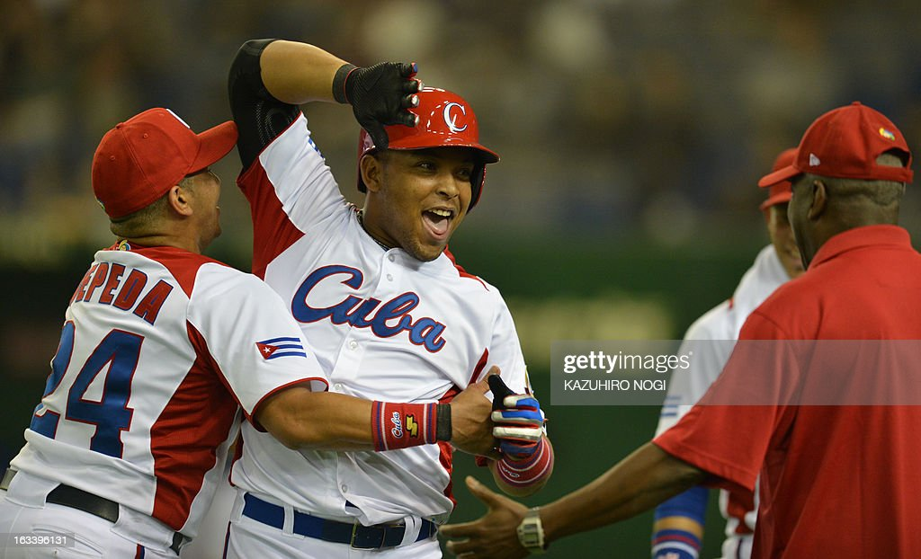 Cuba's outfielder Yasmany Tomas (C) is congratulated by teammate Frederich Cepeda (L) and a coach after his three-run homer against Taiwan during the fourth inning of their second-round Pool 1 game in the World Baseball Classic tournament at the Tokyo Dome on March 9, 2013. AFP PHOTO / KAZUHIRO NOGI