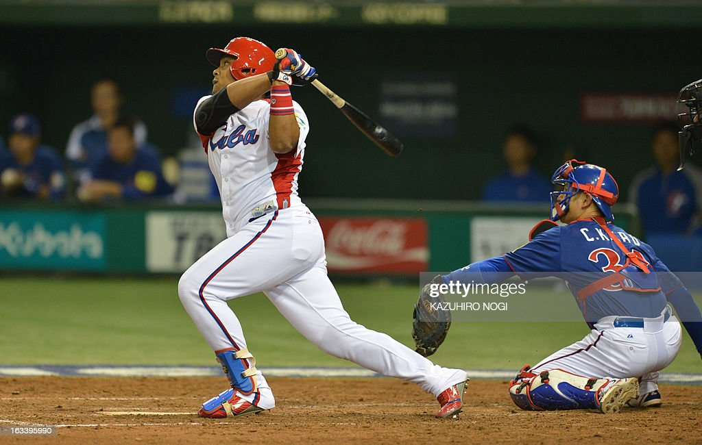 Cuba's outfielder Yasmany Tomas (L) makes a three-run homer as Taiwan's catcher Kao Chih-Kang (R) looks on during the fourth inning of their second-round Pool 1 game in the World Baseball Classic tournament at the Tokyo Dome on March 9, 2013. AFP PHOTO / KAZUHIRO NOGI