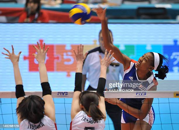 Cuba's Yoana Palacios spikes the ball over Japan's Mai Yamagucjhi and Nana Iwasaka during their women's volleyball qualifying tournament match for...