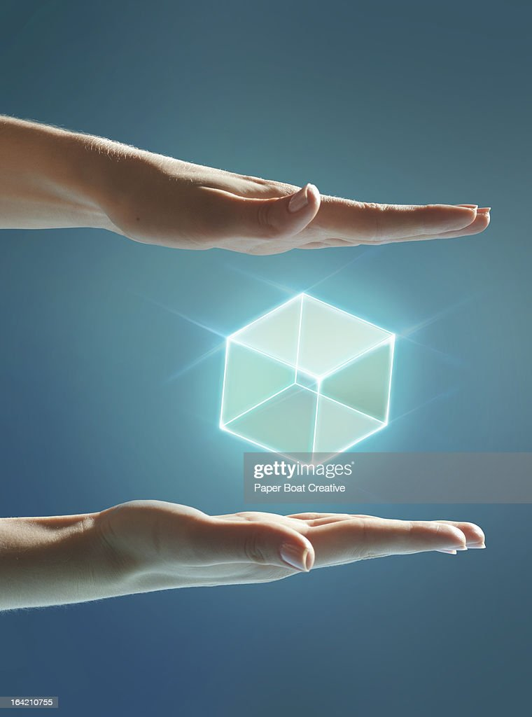 Cube of light floating between hands : Stock Photo