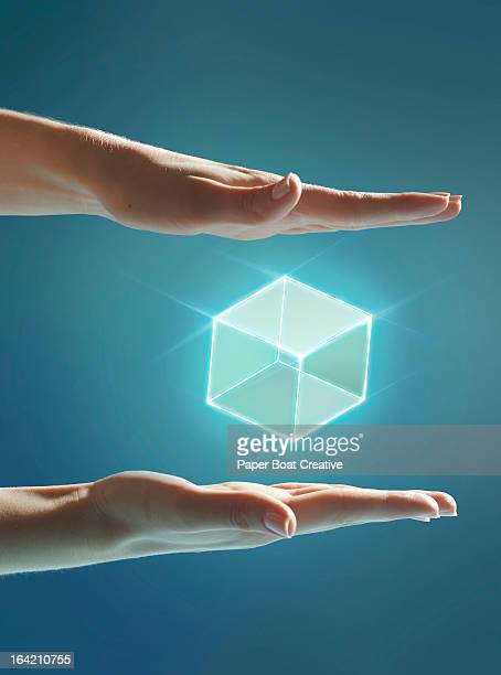 Cube of light floating between hands