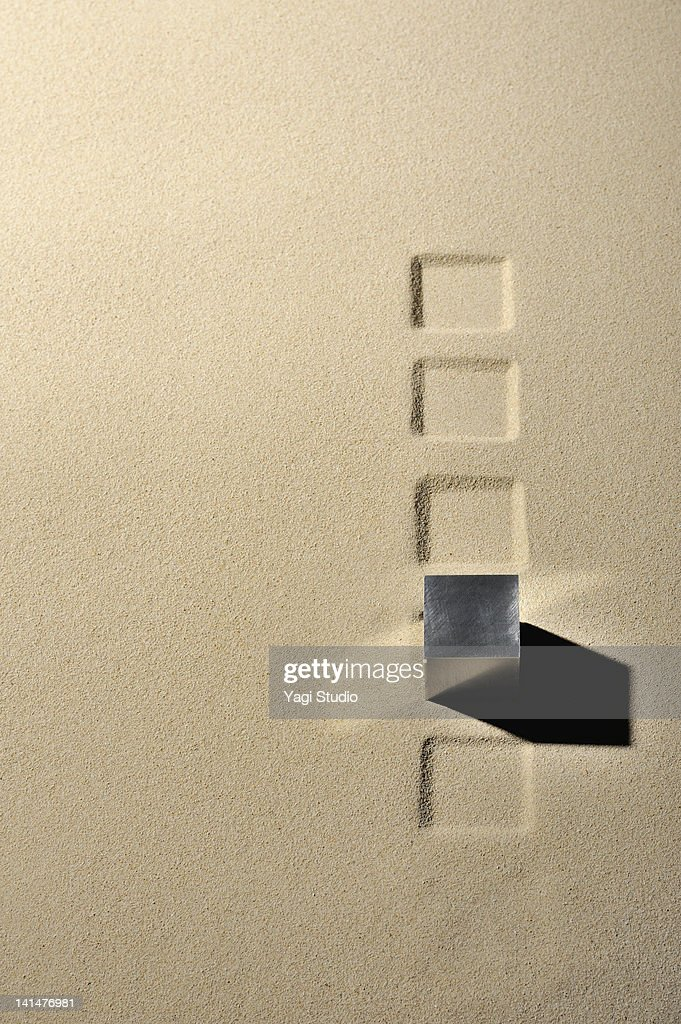 Cube of metal  and mark the square in the sandpit : Stock Photo