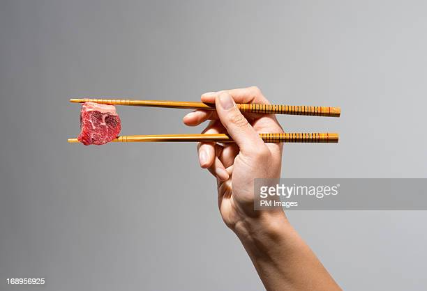 Cube of raw meat in chop sticks