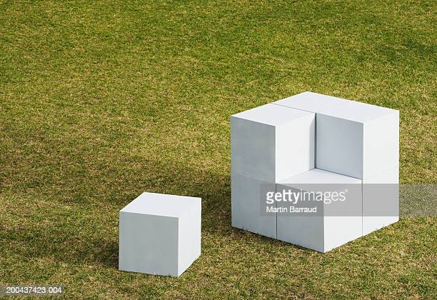 Cube on ground beside giant cube made from smaller cubes, outdoors