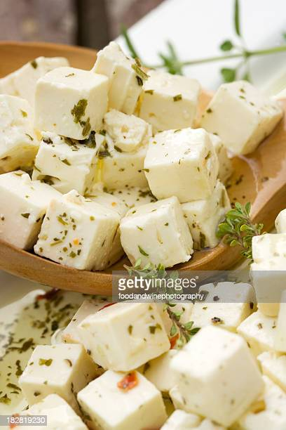 Cubed feta cheese with herbs in a wooden spoon