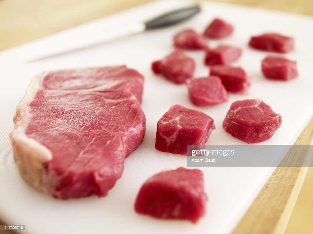 Cubed raw steak on cutting board : Stock Photo
