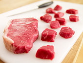 Cubed raw steak on cutting board