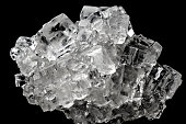 Cubic salt crystal aggregate against black background, isolated