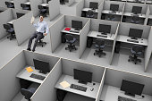 A lone businessman in office chair within a sea of cubicles a concept images illustrating Friday, Vacation, Success, Standing out of the Crowd.