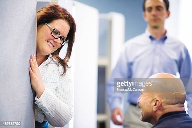 Cubicle workers have fun conversation while supervisor is coming