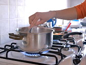 primo  piano di pentole e fornelli durante la cottura di cibo