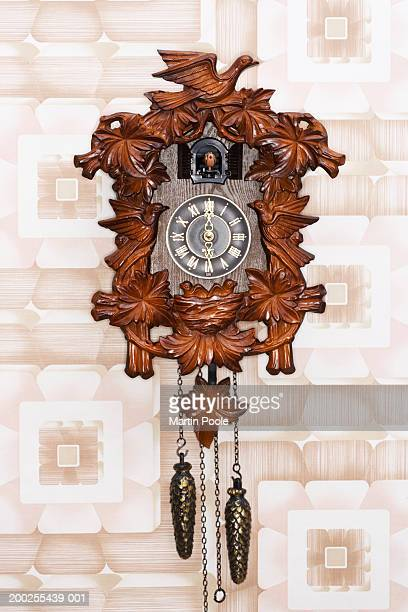 Cuckoo clock hanging on patterned wall