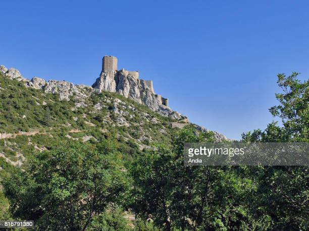 Queribus Castle fortress set high up on a rocky peak at an elevation of 728m and path near Nordsous under the blue sky