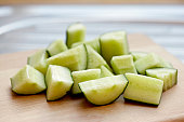 Cucumber chunks on wooden surface, close up