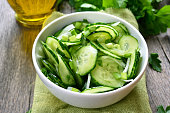 Cucumber salad in white bowl, close up view