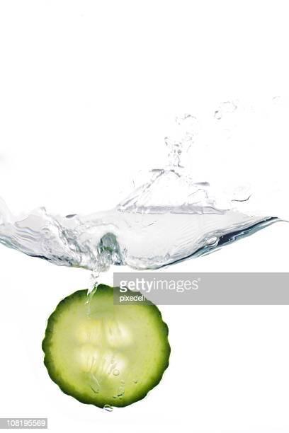 Rondelle de concombre éclabousser dans l'eau, isolé sur fond blanc