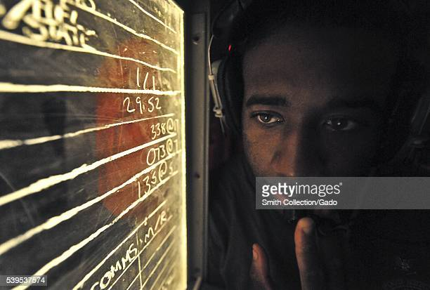 Culinary Specialist 3rd Class Ronald Sampson maintains communications with the bridge from the flight deck control room during flight operations...