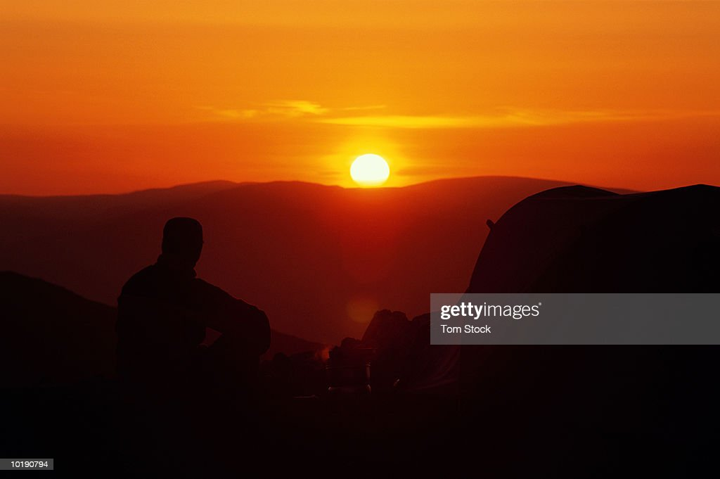 UK, Cumbria, Lake District, Coniston Fells, male camper cooking outsid : Stock Photo