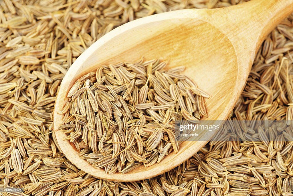 cumin seeds macro and wooden spoon as background : Stockfoto