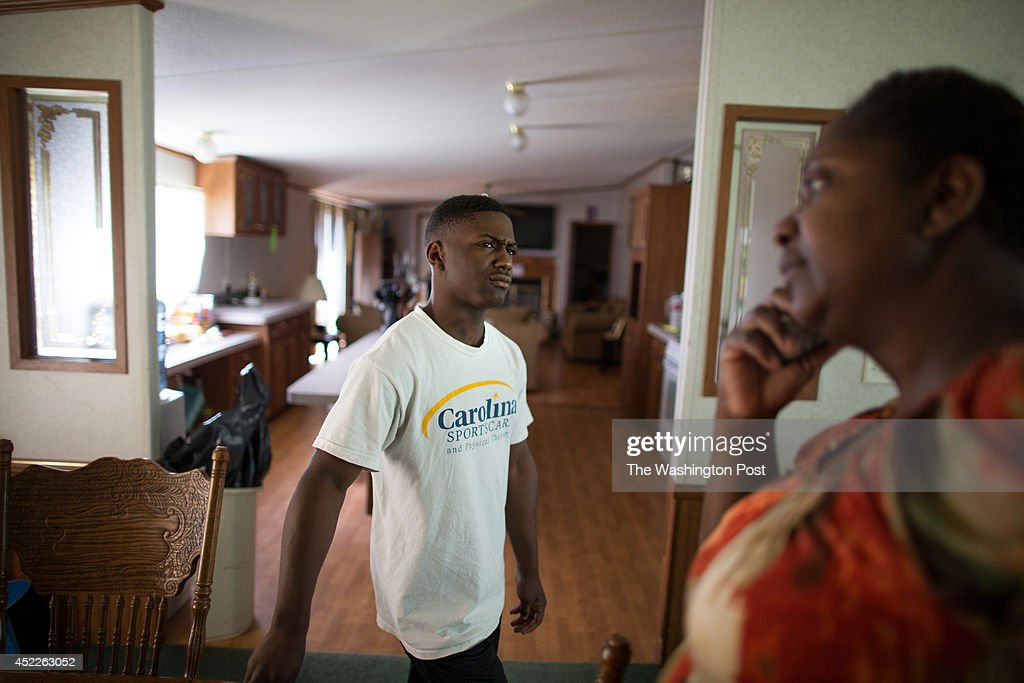 CJ Cummings, center, listens to his mother Savasha Cummings in their home on July 14, 2014 in Beaufort, South Carolina. Cummings is a 14-year-old power lifter who has been lauded as the next great home for an American weightlifting medal at the Olympics.