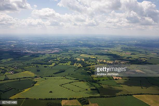 Cumulus clouds float over wheat fields are seen from a plane descending towards Luton airport London