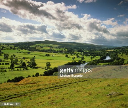 Cumulus clouds gathering over country landscape and river : Stock Photo