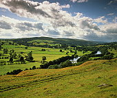 Cumulus clouds gathering over country landscape and river