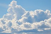 Luminous cloudscape with pale blue sky and white fluffy clouds