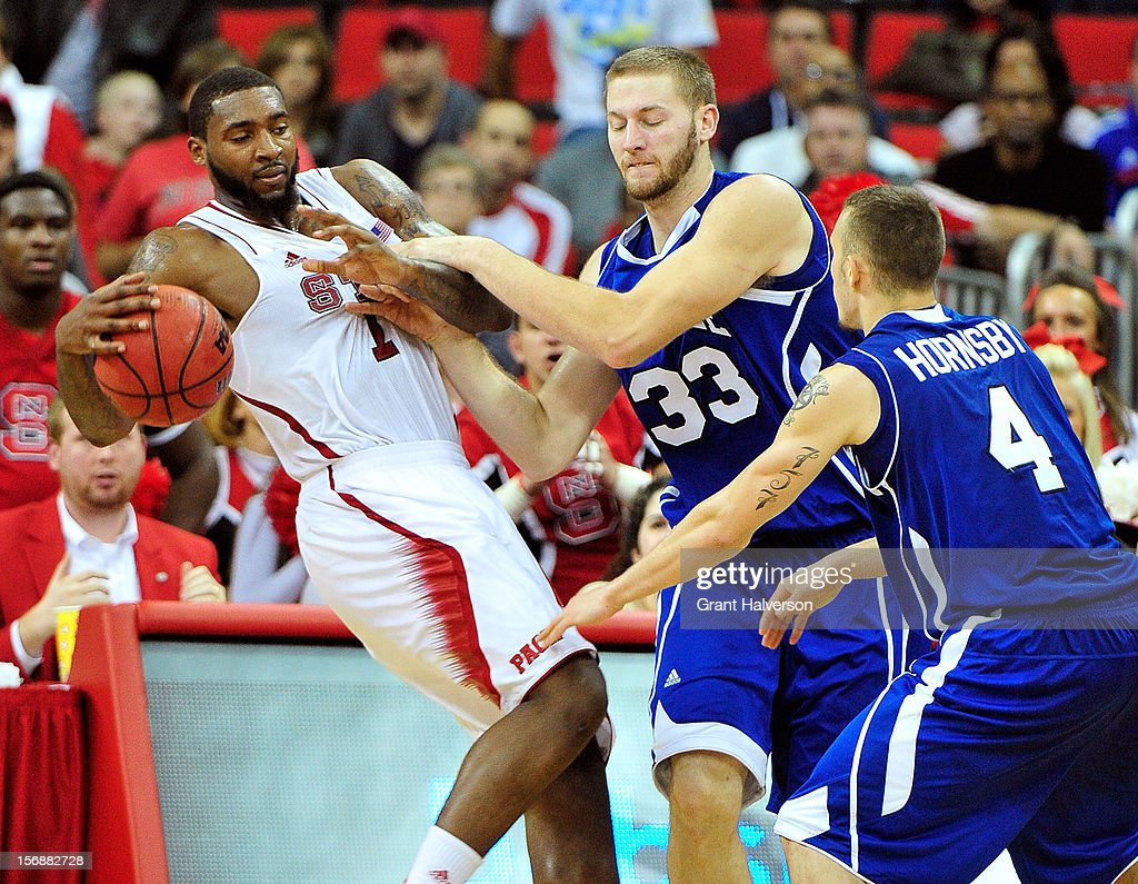 D.J. Cunningham #33 and Keith Hornsby #4 of the North Carolina-Asheville Bulldogs foul Richard Howell #1 of the North Carolina State Wolfpack during the final minute of play at PNC Arena on November 23, 2012 in Raleigh, North Carolina. North Carolina State won 82-80.